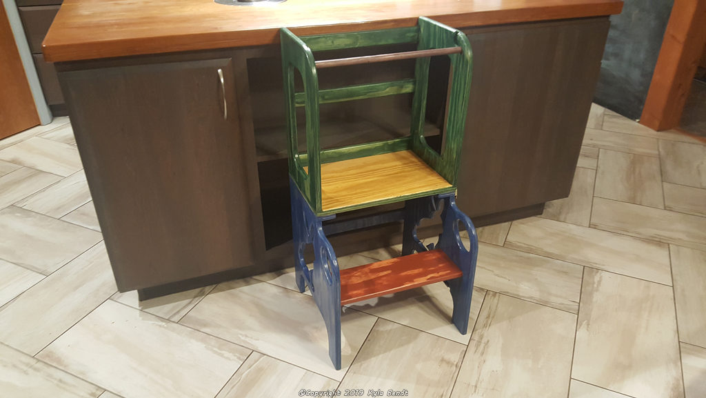 A colorful kid's step stool with bunny cutouts and a safety bar.