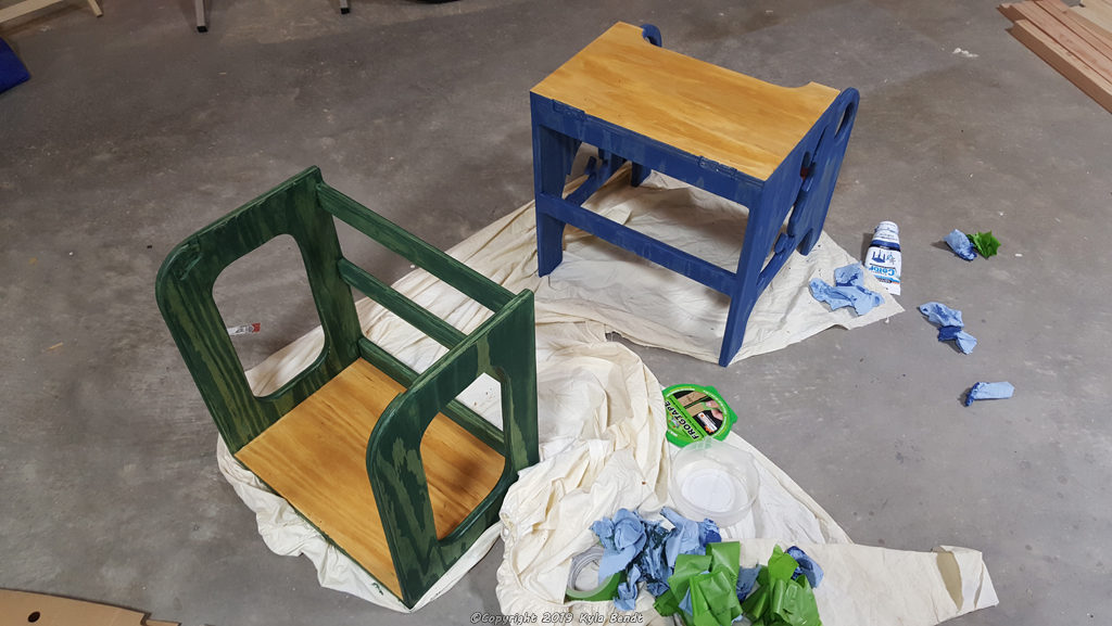 Kid's step stool in two halves still being painted.  The bottom half of the step stool is painted yellow and blue and has bunny cutouts.  The top part is yellow and green.